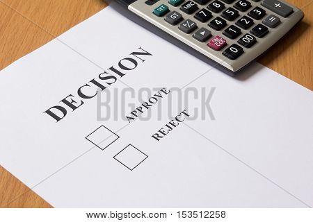 Decision paper (approve reject) with calculator background