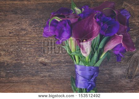 Bouquet of fresh calla lilly and eustoma flowers on wooden table, retro toned