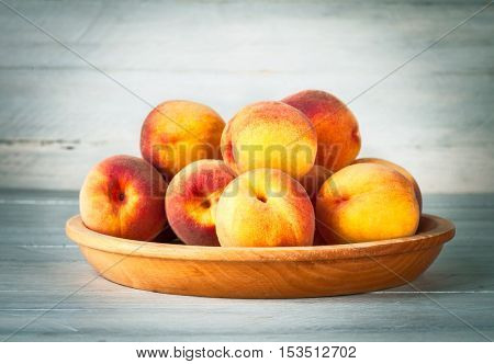 Fresh peach fruits on wooden plate and board in rustic style copyspace