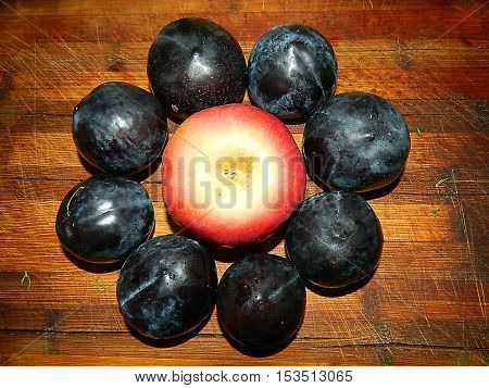 Autumn bright fruit. On a wooden board in the form of a flower lined with blue plums and red apple.