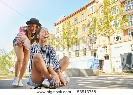 Fun loving young women playing on a skateboard in a residential street low angle view
