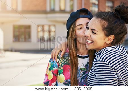 Affectionate trendy young woman kissing her laughing friend on the cheek as they stand on the side of an urban street with copy space