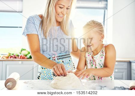 Excited little girl helping her mother make pastry as they knead the dough together at the kitchen counter high key with sun flare