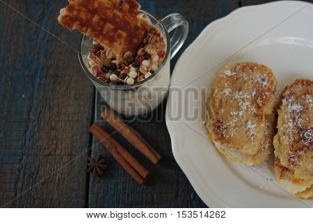 muesli with yoghurt and waffles in a glass Cup, French toast with cinnamon on wooden background