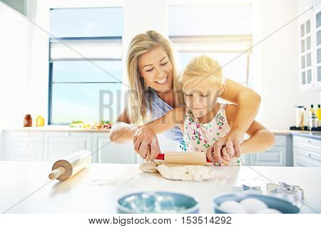 Mother helping her cute little blond daughter to roll pastry with a child size rolling pin as she learns to bake in the kitchen high key with copy space