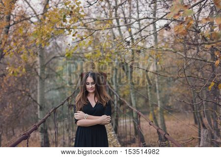 Autumn portrait of a young woman, on a wooden bridge