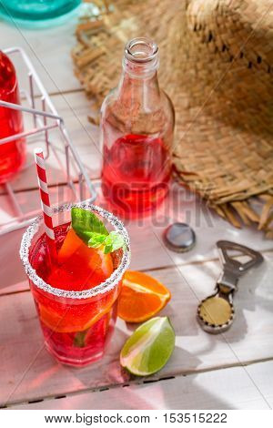 Cold summer drink with citrus fruit on wooden table