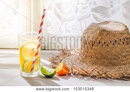 Tasty drink with lemon and orange on wooden table