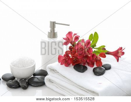 Red branch orchid on roller towel with stones ,salt in bowl,oil