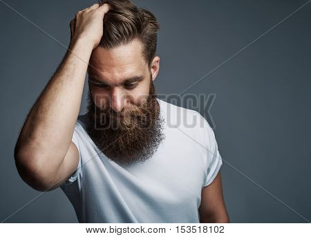 Thinking young man with long beard and white shirt holding hair while facing downward over gray background with copy space
