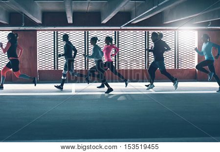 Group of diverse young people urban running in front of the brightly lit grids on the windows of an undercover parking lot
