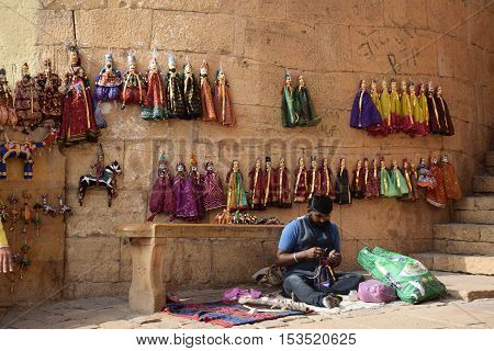 JAISALMER, RAJASTHAN, INDIA - FEBRUARY 10, 2016 - Unidentified indian man preparing and selling handmade pupets inside Jaisalmer fort