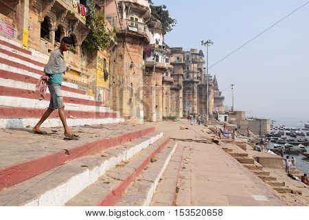 VARANASI, UTTAR PRADESH, INDIA - FEBRUARY 17, 2016 - Unidentified indian guy going down the steps of the ghats towards the holy river Ganga