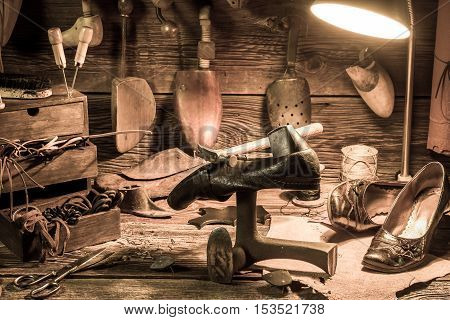 Vintage Shoemaker Workplace With Tools, Shoes And Laces