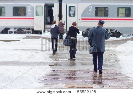 Diverse people getting on a train on a snowy day