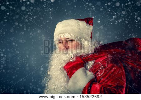 Winking Santa Claus Carries A Bag With Gifts.