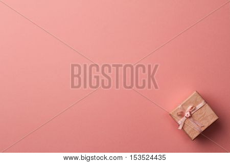 horizontal top view of pink gift box on minimal background of paper textures