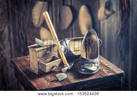 Aged Shoemaker Workplace With Tools, Leather And Shoes