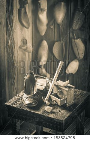 Aged Cobbler Workshop With Shoes, Laces And Tools