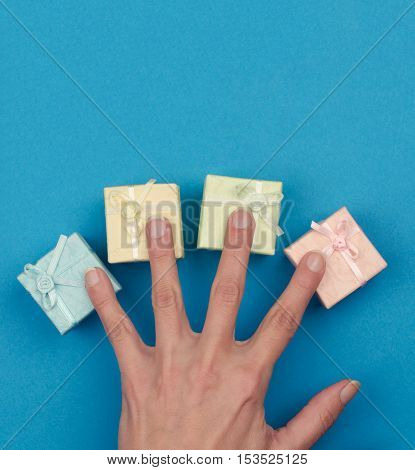 top view hand with the fingers spread across small gift boxes of different colors on blue background