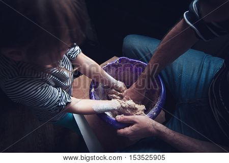 Top view of father and daughter working the dough of a bread together