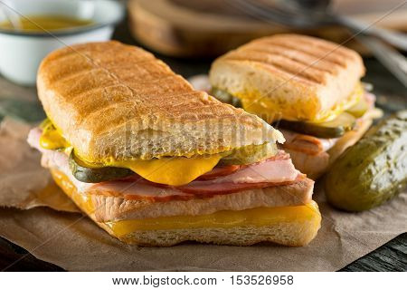 An authentic cuban sandwich on pressed medianoche bread with pork ham cheese pickle and mustard.
