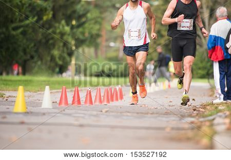 Group of unrecognizable runners sprinting outdoors. Sportive people training in a urban area, healthy lifestyle and sport concepts.