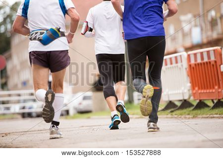 Group of unrecognizable runners sprinting outdoors. Sportive people training in a urban area, healthy lifestyle and sport concepts. Rear view.