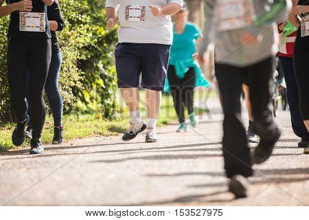 Group of unrecognizable runners sprinting outdoors. Sportive people training in a urban area. Healthy lifestyle and sport concepts.