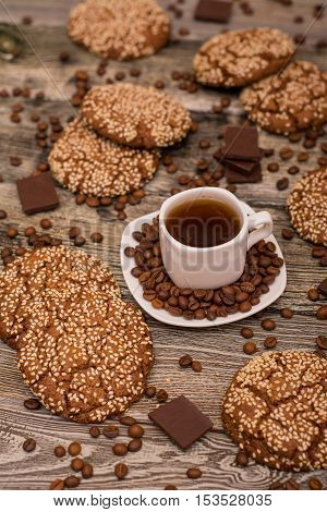 Small white cup of coffee roasted coffee beans cookies with sesame seeds slices of chocolate on wooden background