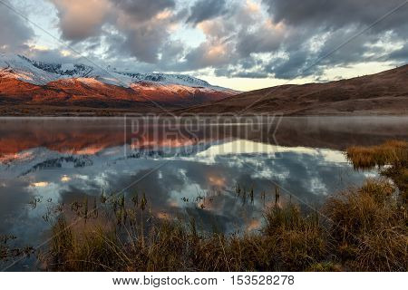 Bright picturesque autumnal view with a beautiful lake in the steppe fog snow covered mountains and the forest and their reflections on a background of sky and clouds at sunrise