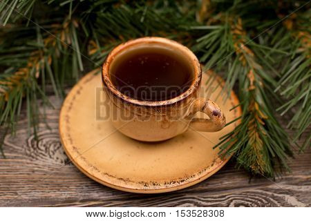 Small cup of coffee and fir branch on wooden background