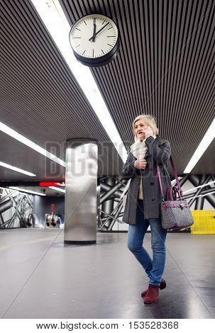 Beautiful senior woman walking in the underground, waiting, talking on the phone