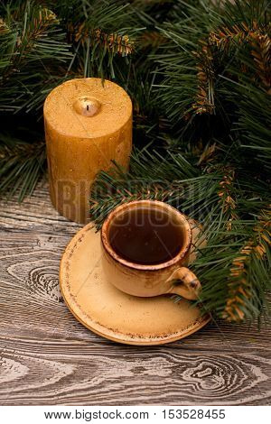 Small cup of coffee candle and fir branch on wooden background