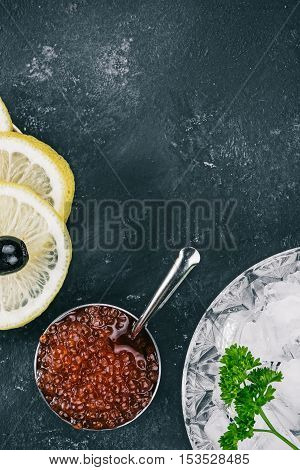 Salted salmon roe in the little steel bowl, ice and lemon slices over spotty black background. Closeup. Flat lay
