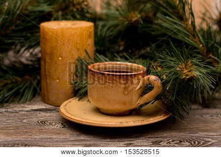 Small cup of coffee fir branch and candle on wooden background