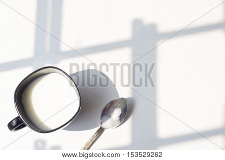 black cup of milk on a natural white background top view