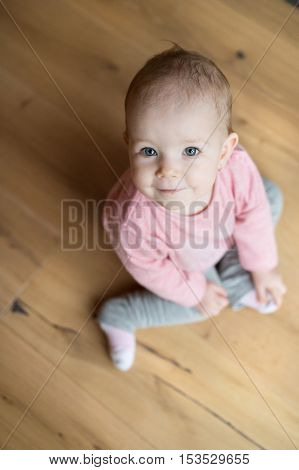 Cute little girl in pink sweatshirt at home sitting on wooden floor, looking up, smiling
