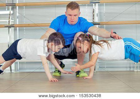 Group of children doing kids gymnastics in gym with nursery teacher.