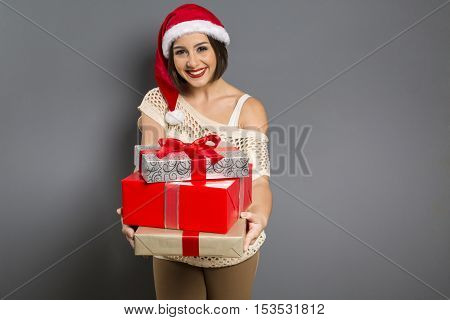 Christmas Woman Portrait Holding Christmas Gift. Smiling Happy Girl Over Grey Background