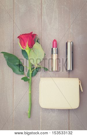 Still life with wallet, rose flower and red lipstick, retro toned