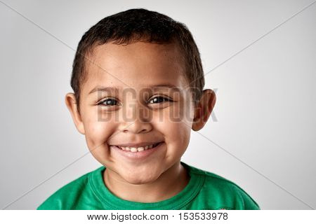 Mixed race boy smiling portrait child in studio