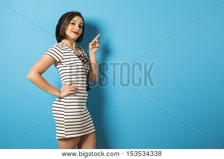 Fashion Young Girl Pointing Finger. Blue Background.