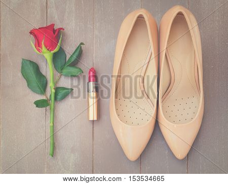 Nude colored high heels still life with red rose bud and lipstick, top view, retro toned