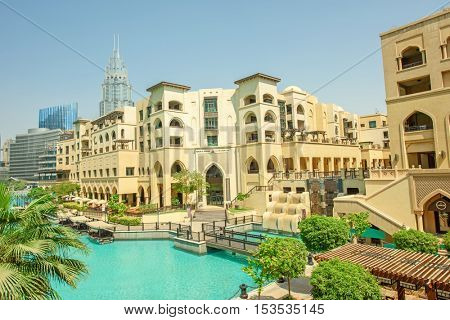 DUBAI, UAE - OCTOBER 11, 2016: A view of Souk al Bahar and the turquoise Burj Khalifa Lake surrounded by greenery