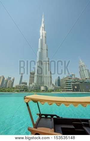 DUBAI, UAE - OCTOBER 11, 2016: A view of The Burj Khalifa and a water boat (abra) surrounded by greenery in the turquoise lake of Burj Khalifa