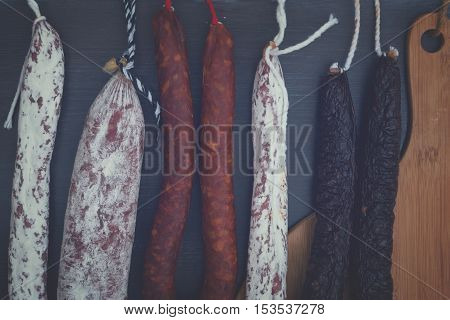 Cured meat and sausages hanging on black wooden background close up, retro toned