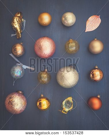 Christmas golden decorations pattern on dark wooden background, top view, retro toned