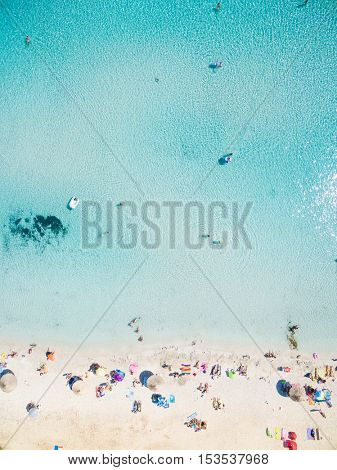 Aerial view of sandy beach with tourists swimming in beautiful clear sea water