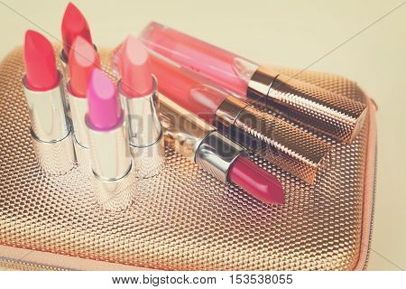 Collection of colorful lipsticks on golden woman pursue bag, retro toned